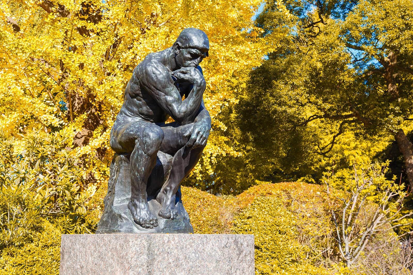 Der Denker als Bronzefigur auf einem Steinsockel.