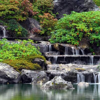 Wasser fließt über arrangierte Stein in einen See