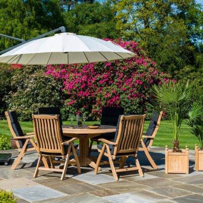 Holzmöbel in perfekter Kombination mit Steinboden und farbenfrohen Blumen