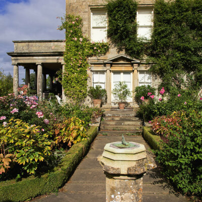 Bepflanzter Garten und Sonnenuhr vor Vintage-Villa © Fotolia.com