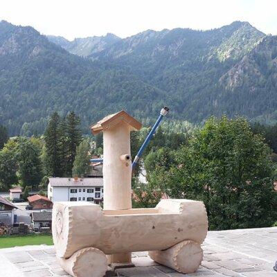 Geschnitzter Holzbrunnen