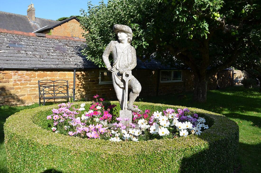 Gärtner-Statue in Blumenbeet