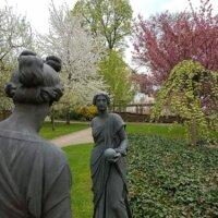 Frauenskulpturen in blühendem Garten