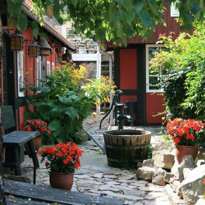 Gartenbrunnen aus Holz in blühendem Garten