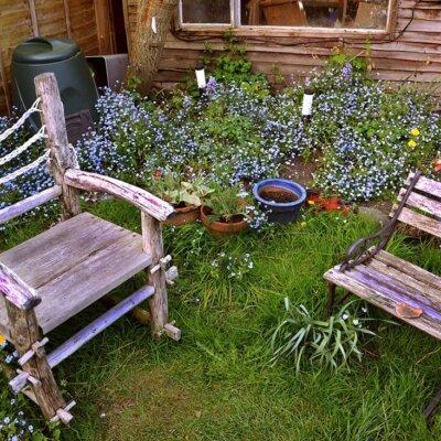 Kleine Sitzgelegenheiten laden im Garten zum Verweilen ein