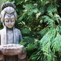 Asiatische Statue neben immergrünen Pflanzen
