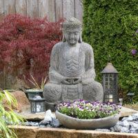Buddha im Garten dekorativ drapiert