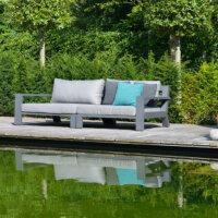 Sofas und Sonnenliegen laden am Schwimmteich zum Entspannen ein.