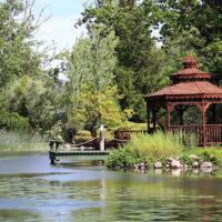 Gartenpavillon in rötlichem Holz direkt am Wasser.