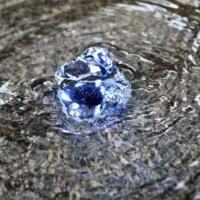 Beleuchtetes Sprudel-Element im Brunnen.