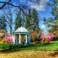 Historischer Gartenpavillon im blühenden Garten.