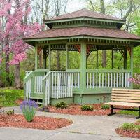 Gartenpavillon aus grün gestrichenem Holz in perfekter Harmonie mit dem Garten.