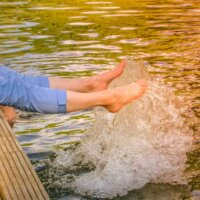 Ein kleiner Steg erleichtert das Ein- und Aussteigen aus dem Schwimmteich.