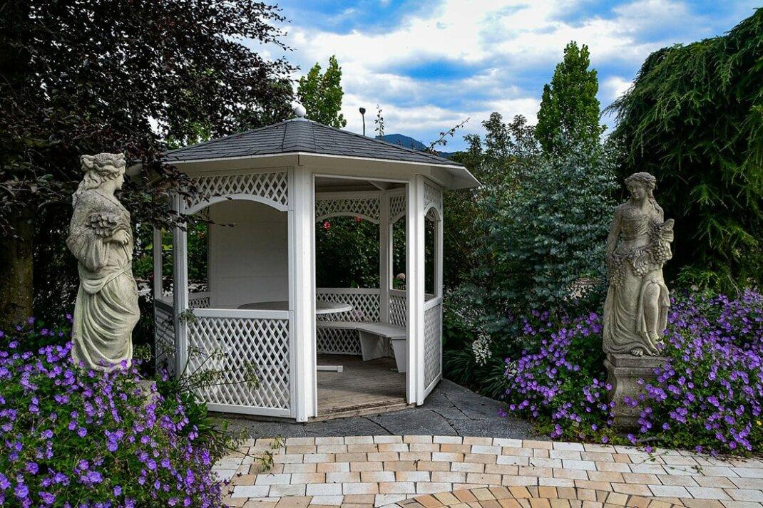 Romantischer Gartenpavillon umhüllt von blühenden Büschen