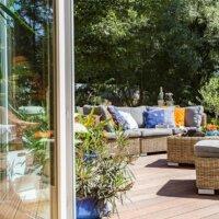 Sommerliche Terrasse mit Holzdielen und Möbeln aus Naturmaterialien