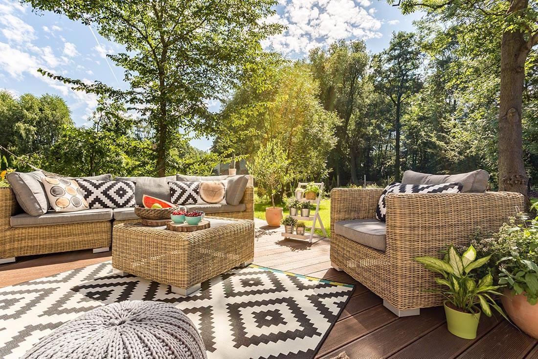 Terrasse mit Holzdielen und schwarzweißem Teppich