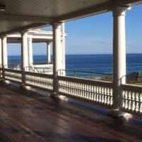 Terrasse mit dunklen Holzdielen und weißem Geländer