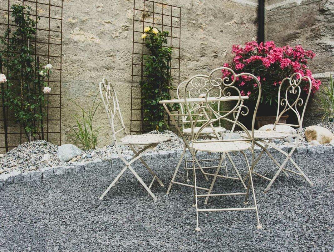 Romantisch gestaltete Terrasse mit Sichtschutz aus Naturstein und Pflanzen