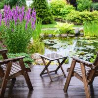 Gartenterrasse mit Teich und Gartenmöbeln