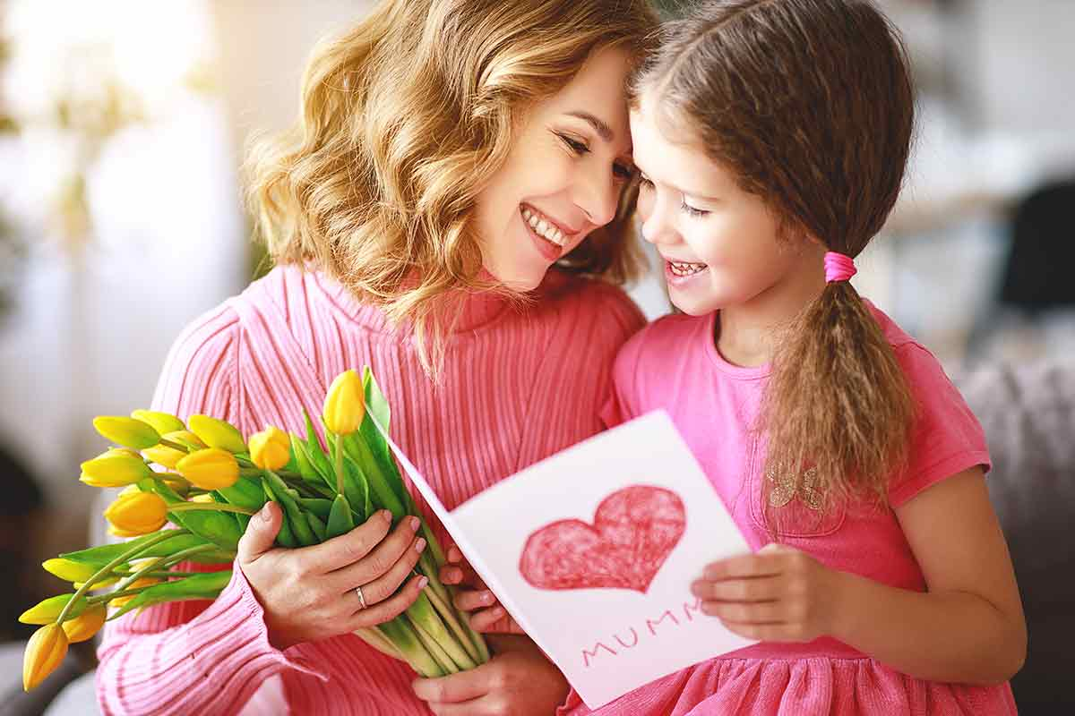 Süße Tochter überrascht Ihre Mama mit einem schönen Spruch zum Muttertag