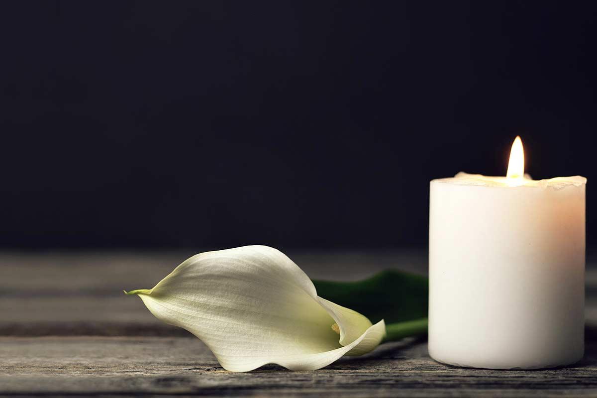 Eine Kerze und eine schöne Blume erinnern zum Muttertag an eine verstorbene Mutter