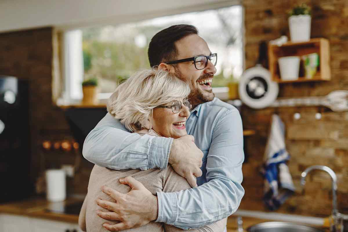 Mutter und ihr erwachsener Sohn freuen sich zusammen zum Muttertag über die gemeinsame Zeit und schöne Muttertagssprüche