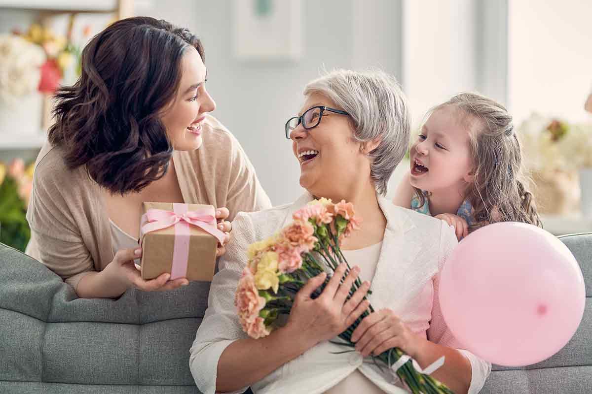 Mutter, Tochter und Großmutter freuen sich zusammen über schöne Sprüche und Geschenke zum Muttertag