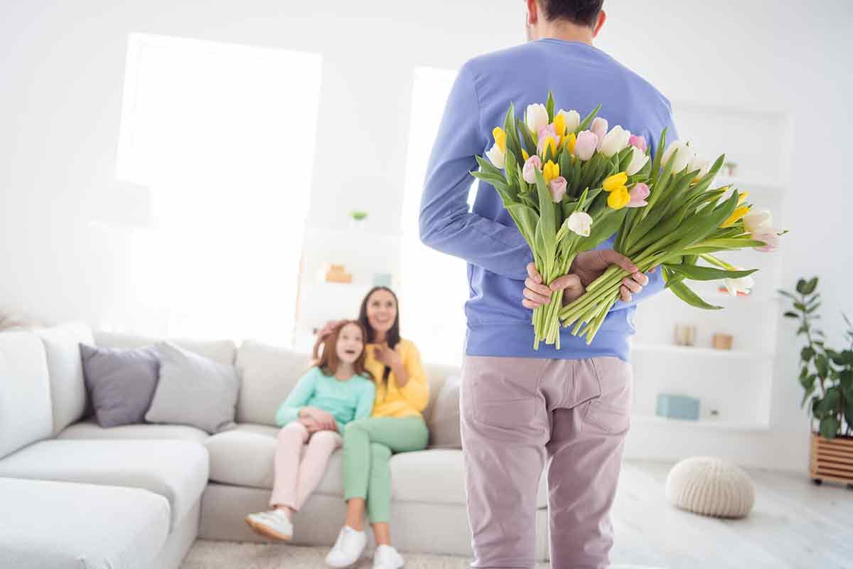 Ehemann übergibt Frau zum Muttertag schöne Blumen und Karte mit schönen Muttertagssprüchen