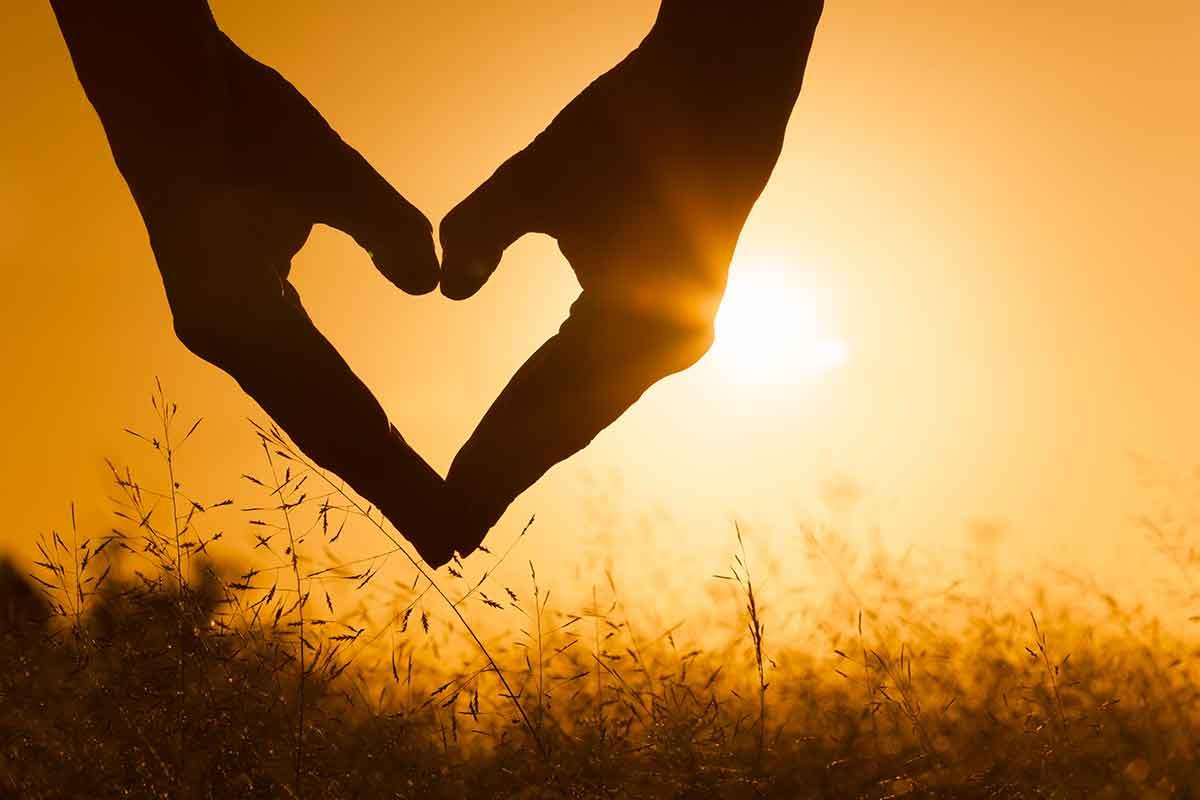 Zwei Hände formen Herz vor Sonnenuntergang passend zu nachdenklichen Sprüchen zum Muttertag