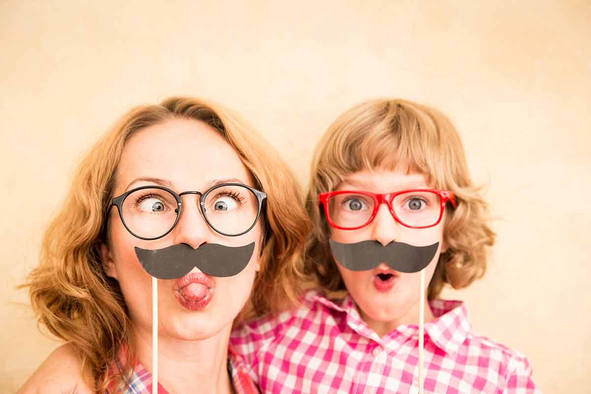 Mutter und Kind ziehen Grimassen und freuen sich über lustige Muttertagssprüche