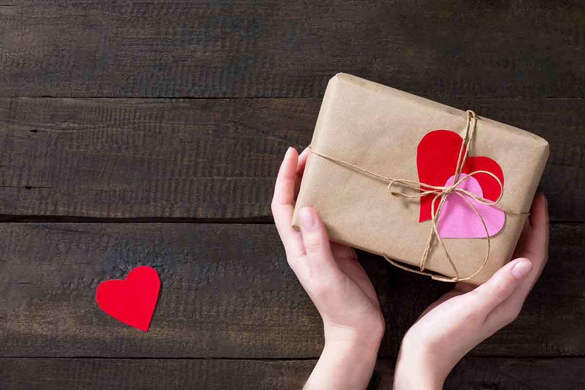 Hände halten Paket mit kleinem Geschenk und schöner Karte zum Muttertag mit liebevollen Sprüchen