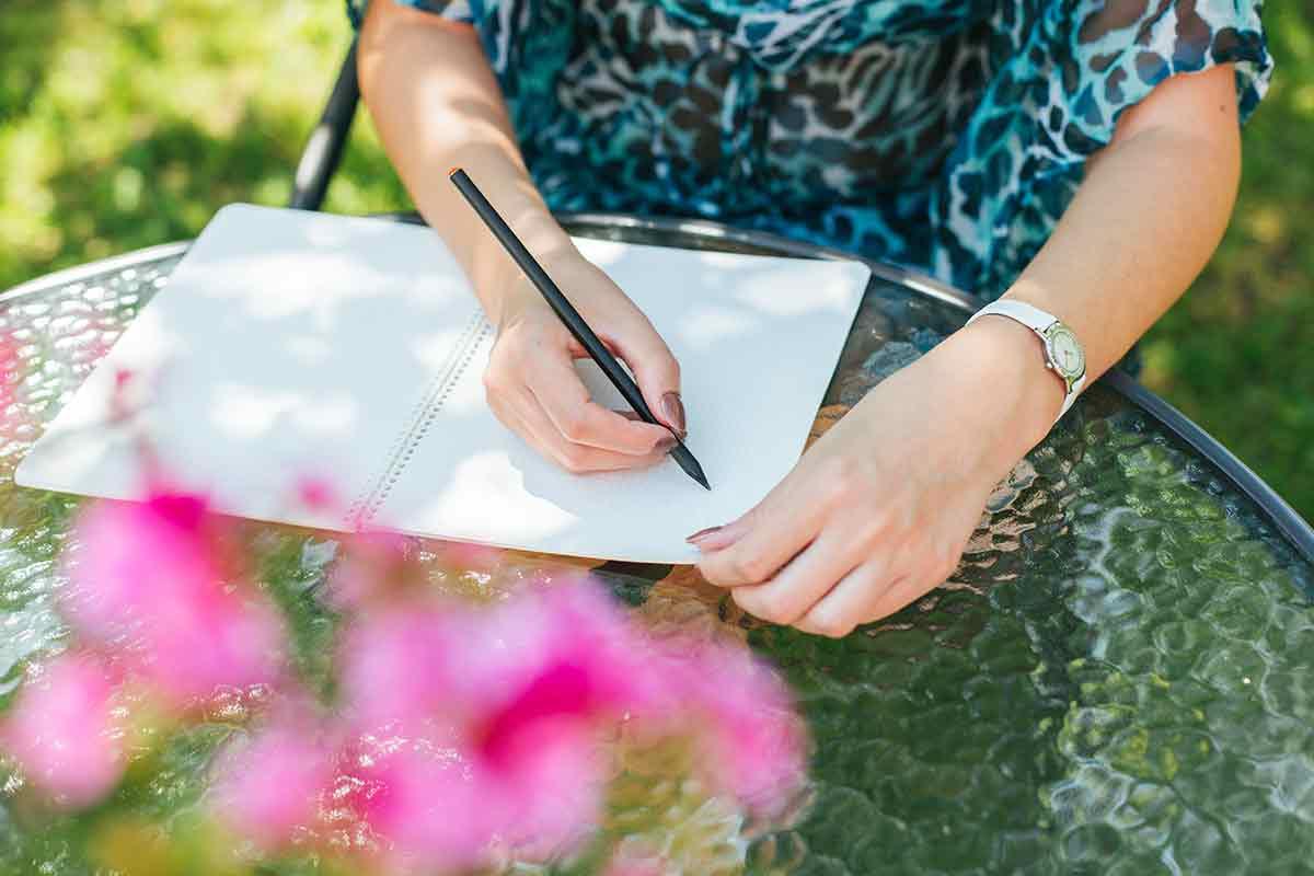 Frau schreibt Gedichte und Zitate zum Muttertag im Garten in Ihren Block