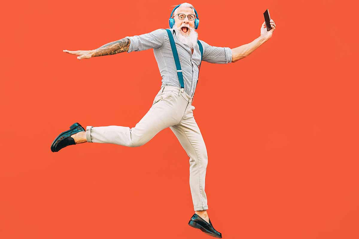 Hipper Vater springt mit Smartphone