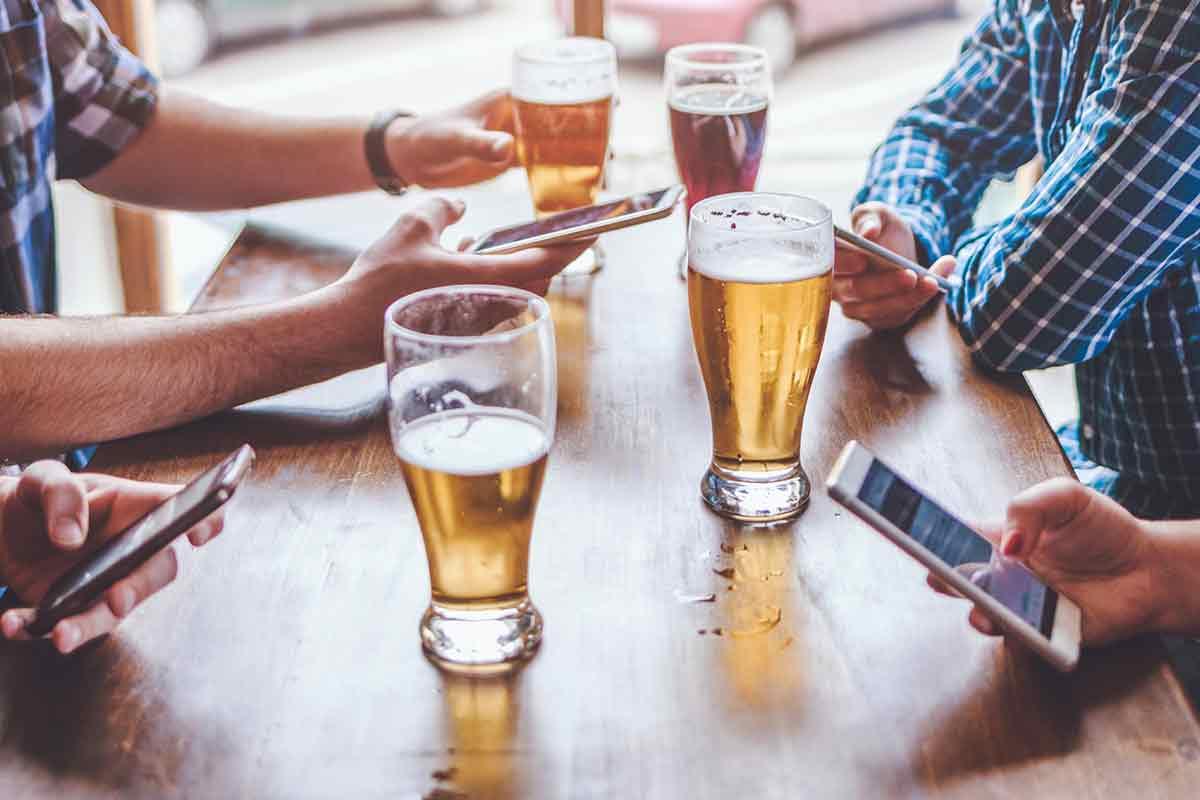 Männer lesen Vatertagssprüche auf Handys mit Bier
