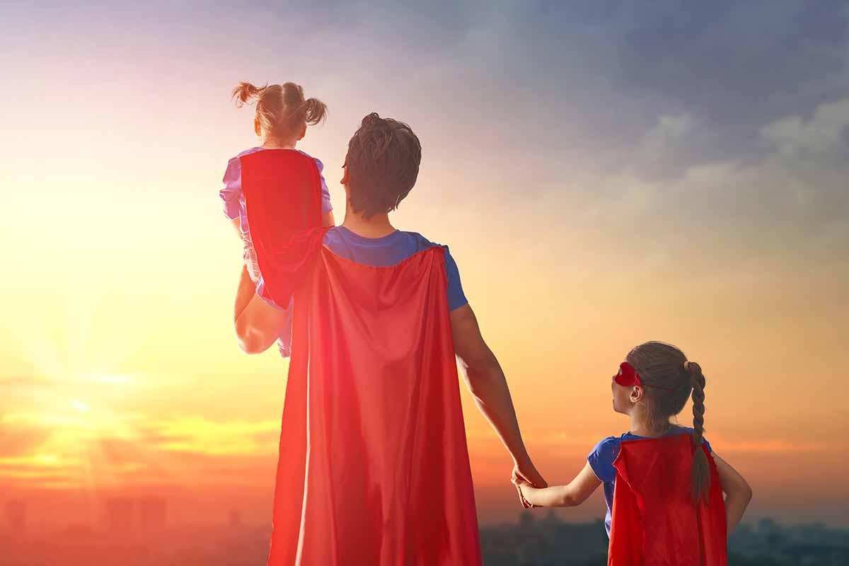 Vater in Superman-Kostüm mit 2 Töchtern