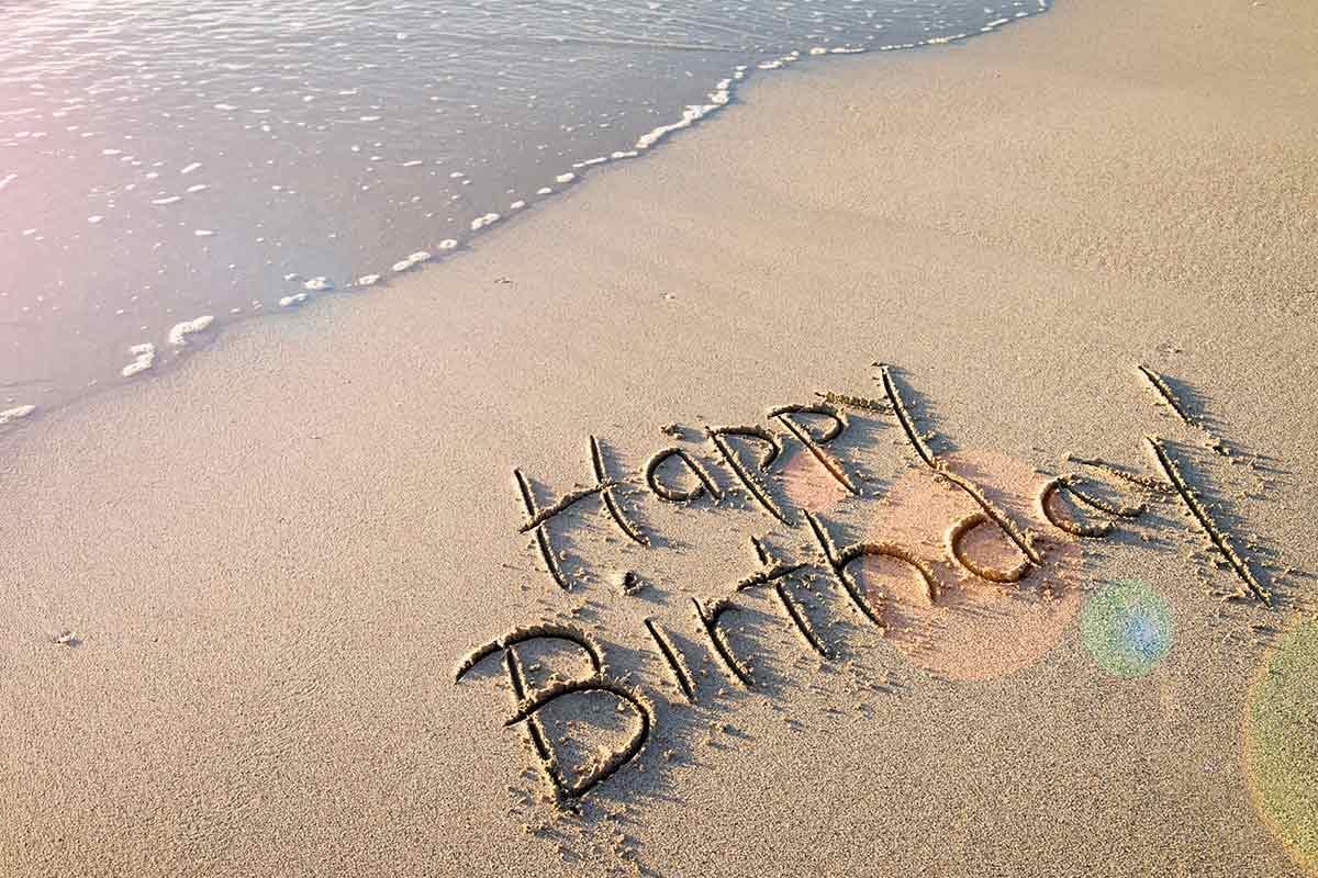 Happy Birthday auf Stand in Sand gemalt