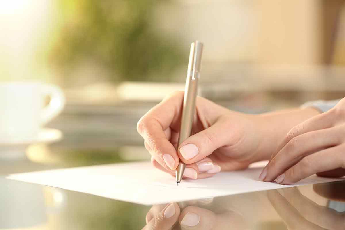Hand schreibt Brief und schöne Geburtstagssprüche