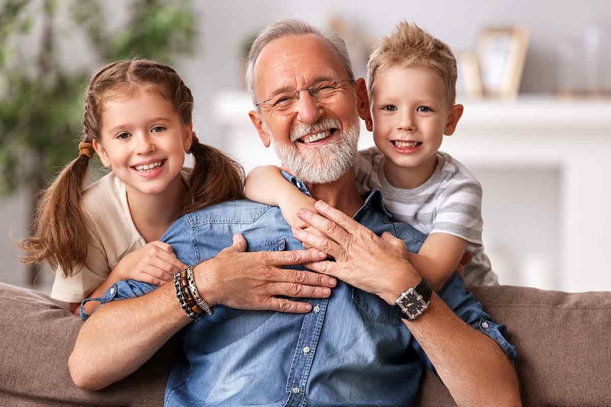 Fröhlicher Opa mit Enkelkindern auf Couch