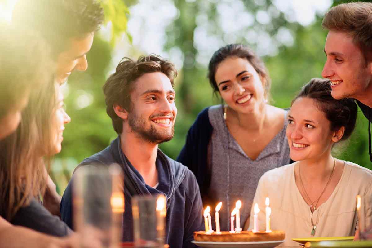 Junger Mann freut sich mit Freunden über Geburtstag