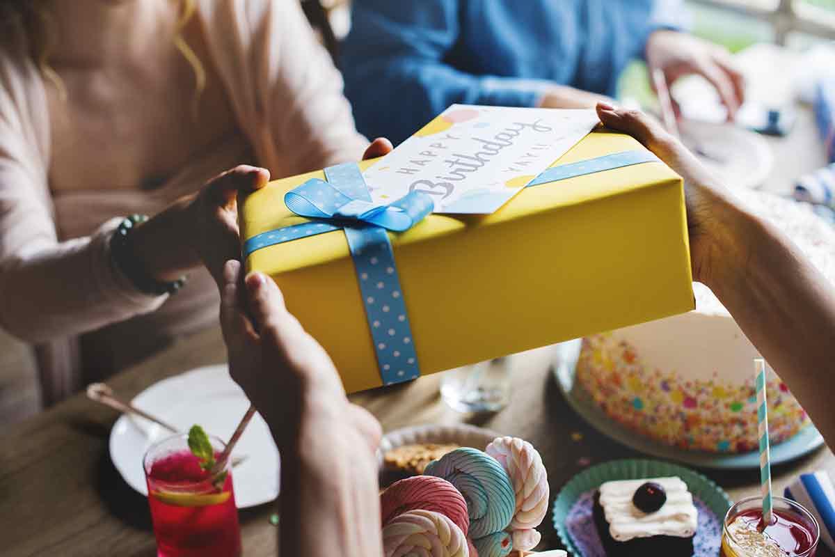 Hände übergeben Geburtstagsgeschenk mit Karte und Geburtstagsspruch