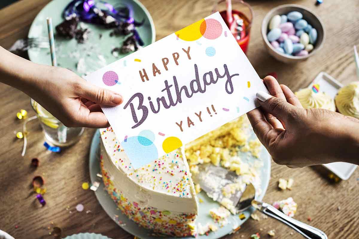 Hände überreichen Geburtstagswünsche per Karte