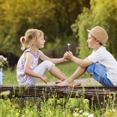Junge und Mädchen sitzen in der Blumenwiese