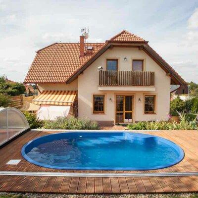 Ovaler Pool vor einem Einfamilienhaus