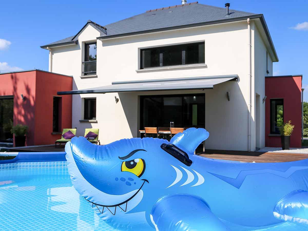 Pool mit Spielzeug-Hai vor Haus