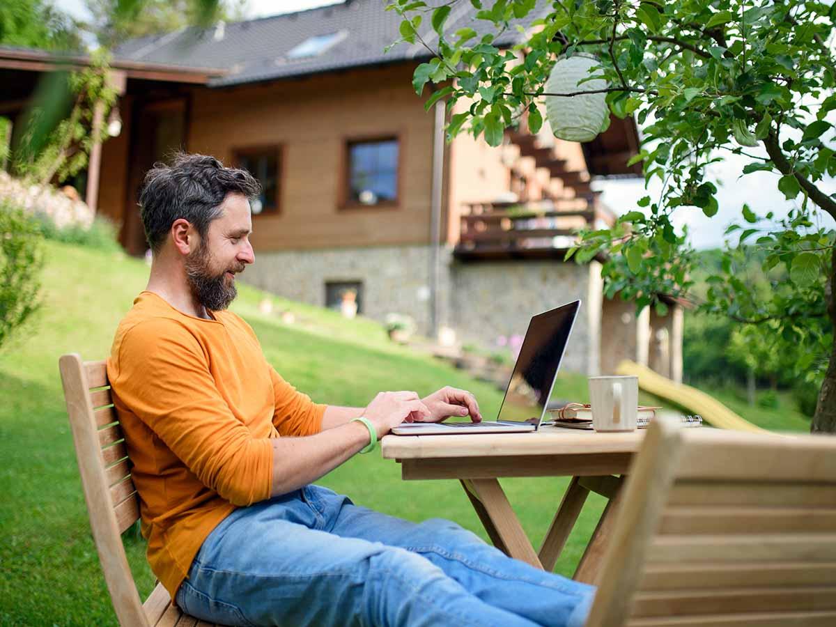 Mann bestellt GfK-Pools mit Laptop in Garten