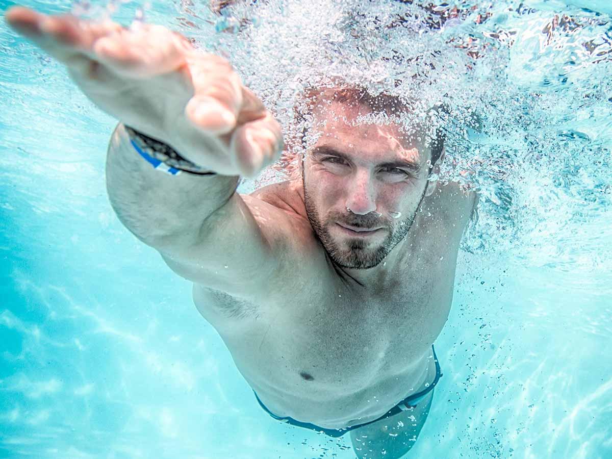 Mann schwimmt in GfK-Pool mit Gegenstromanlage