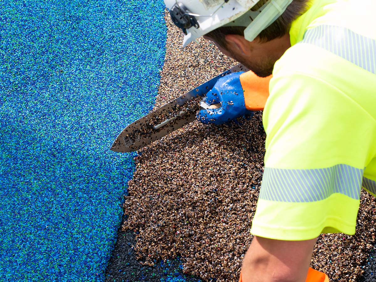 Bauarbeiter bearbeitet Boden auf Kinder-Spielplatz