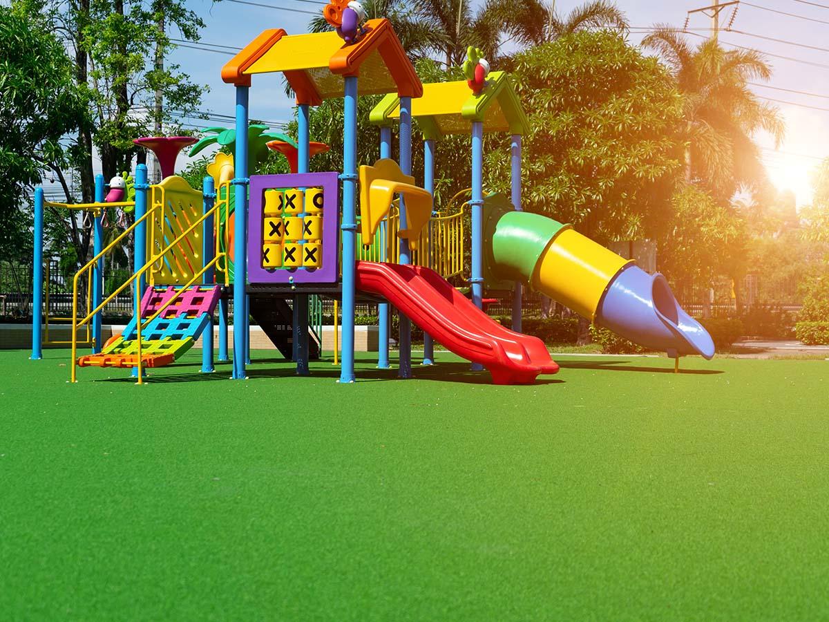 Bunter Kinder-Spielplatz aus Kunststoff auf grünem Rasen
