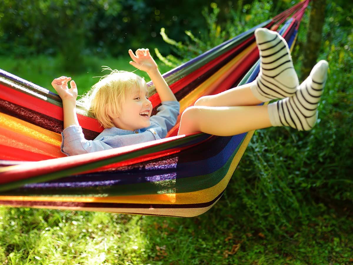 Mädchen entspannt sich in bunter Hängematte in Garten