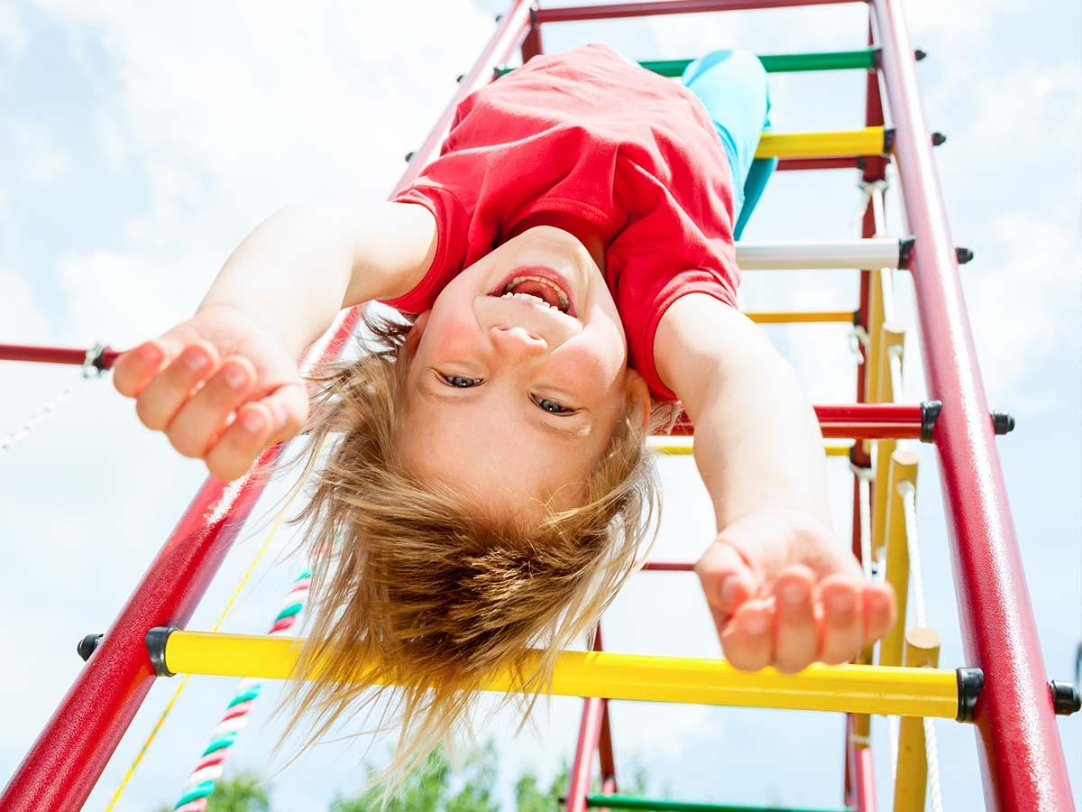 Mädchen hängt kopfüber an Klettergerüst auf Spielplatz